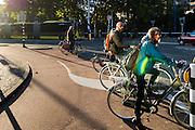 Fietsers wachten bij het Ledig Erf in Utrecht bij het verkeerslicht.<br /> <br /> Cyclists waiting at a traffic light at Ledig Erf in Utrecht.
