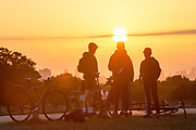 UNITED KINGDOM, London: 20 July 2020 <br /> Members of public watch the sun as it rises over the London skyline earlier this morning from Richmond Park. The weather is set to be sunny in the capital city over the next few days.