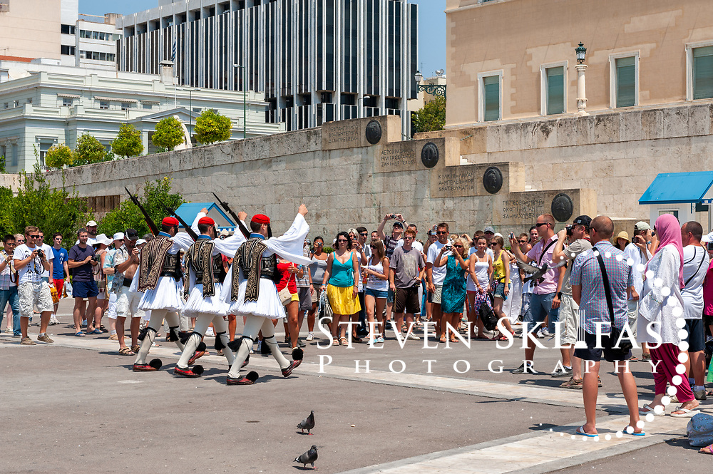 Syntagma square. Athens. Greece. View of Greek Evzones arriving to perform the very slow and highly stylized ceremonial changing of the guard at the monument to the Unknown Soldier in Athens. The monument to the Unknown Soldier, erected in 1929-1932, depicts a relief of a dying Greek solider and is watched around the clock by pairs of Evzones, elite members of the Presidential ceremonial guard unit, standing motionless outside their sentry boxes wearing traditional dress. These guards are wearing the full dress uniform consisting of a white, bell-sleeved shirt and a white foustanella with 400 pleats (Symbolising the 400 years of Ottoman occupation). It is only worn on Sundays or important national holidays.