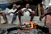 Fishermen light a fire to keep warm in the early morning.  The small fishing village of Machimaar Nagar struggles to hold on as the explosive growth of Mumbai begins to encroach on its space.