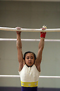 A Girl on China's national gymnastics team trains on the uneven bars in Beijing. China has ordered its national gymnasts to turn in their computers and car keys, turn off their cell phones at 10 p.m. and stay in at night, so they will be fresh for training the next day.