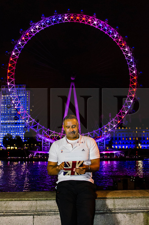 © Licensed to London News Pictures. 19/07/2012. London,UK.  London Eye Light Show.  Decathalon winner Daley Thompson stands before a London Eye illuminated in the colours of the Union Jack, carrying a Union Jack iPad.  EYE ON THE GAMES: Daley Thompson kicks off the world's first social media driven light show at the EDF Energy London Eye, powered by the UK's tweets on London 2012. The first EDF Energy of the Nation result reveals the nation is 62% positive about the Games with a week to go.    www.edfenergyofthenation.com  . Photo credit : Richard Isaac/LNP