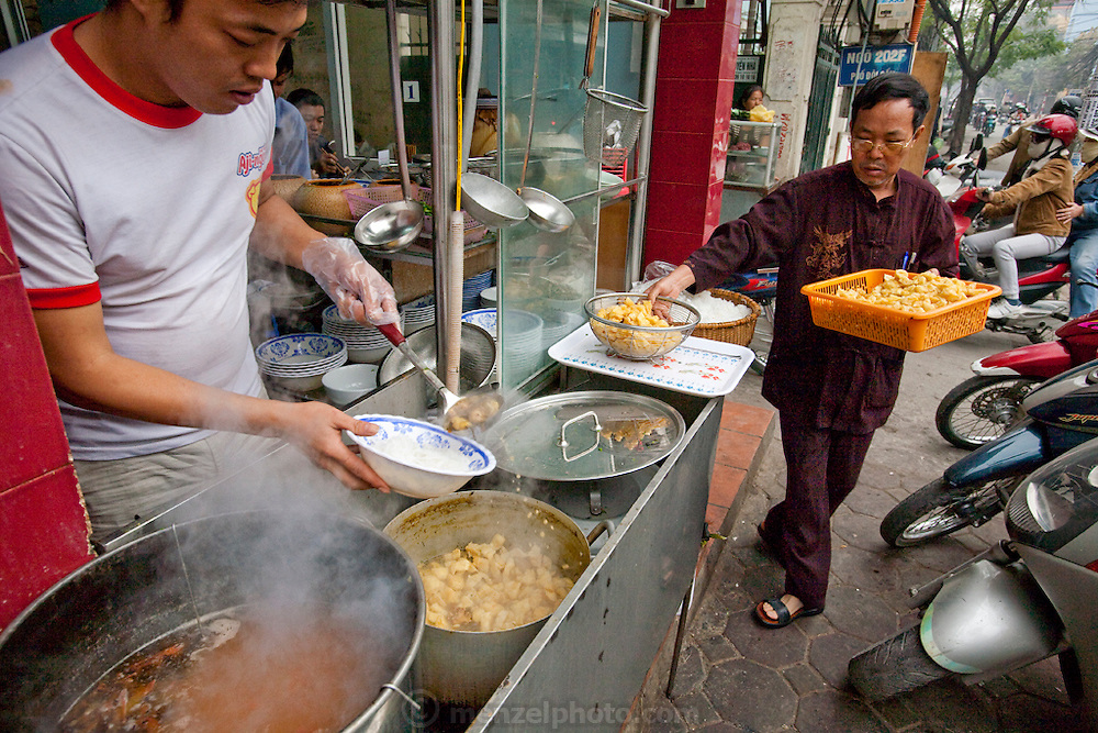A man prepares a dish of pho noodle soup for a customer at a roadside food outlet in Hanoi, Vietnam.