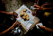"""Laborers play """"golpeado"""" betting the biscuits they get from their company at their dormitories in Guañape Norte Island in the coast off Peru, April 2009."""