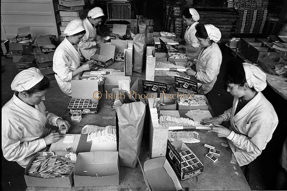 """17/01/1963<br /> 01/17/1963<br /> 17 January 1963<br /> Interiors of Liam Devlin and Sons Ltd. Dublin Sweet Factory at Cork Street, Dublin. Image staff packaging candy sweet-cigarettes, note the boxes of """"cigarette cards"""" that were in each packet. Those visible are a series of gun dogs."""