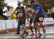 The Medtronic Twin Cities Marathon- Two runners assist an exhausted runner across the finish line in St. Paul.