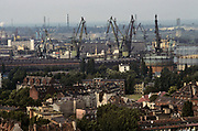 Seen from St Catherine's Church in the old city of Gdansk, Poland, the famously sprawling shipyard is seen from across the city's old housing and trees. Once known as the Lenin Shipyard but still the largest of its kind in modern Poland. Here in 1980 the union Solidarity (Solidarnosc) was conceived and was partly responsible for a growing dissent against Communist rule, ultimately contributing towards the fall of the Berlin Wall. Lech Walesa started his political career as an electrical technician here, going on to lead Solidarity and then to become President of a democratic Poland. Today Gdansk is a major industrial city and shipping port.