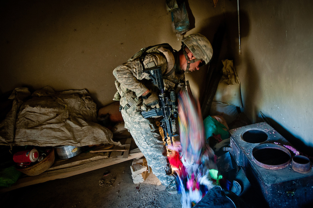An American soldiers dumps clothing on the floor while searching an Afghan home in the Tangi Valley after an IED explosion on a nearby road. explosion on a nearby road.