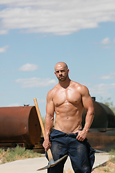 shirtless muscular bald man with a heavy tool