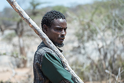 27 January 2019, Burka Dare IDP site, near Micha, Seweyna woreda, Bale Zone, Oromia, Ethiopia: A man carries a stick as he walks through the Burka Dare site for internally displaced people. The Lutheran World Federation supports internally displaced people in several regions of Ethiopia, through emergency response on water, sanitation and hygiene (WASH) as well as long-term development and empowerment projects, to help build resilience and adapt communities' lifestyles to a changing climate.