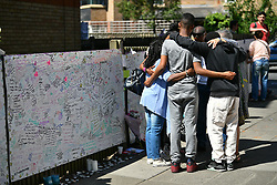 © Licensed to London News Pictures. 17/06/2017. London, UK. A group of local residents hug near The scene of a fire at the Grenfell tower block in west London earlier this week. The blaze engulfed the 27-storey building killing 12 - with 34 people still in hospital, 18 of whom are in critical condition. The fire brigade say that they don't expect to find anyone else alive. Photo credit: Ben Cawthra/LNP