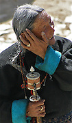This was a traveling pilgrim, an elder TIbetan woman walking in prayer in downtown Lhasa TIbet near a monastery