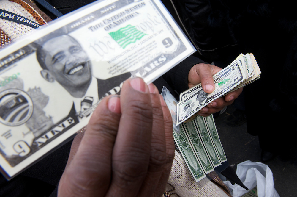 Vendors hawk Barack Obama commemorative money bills on the day of Barack Obama's historic Presidential inauguration.  An estimated two million people flocked to Washington D.C. for the ceremony, enduring freezing temperatures to witness Obama take the oath of office becoming the first African-American to become President, the 44th in the history of the United States of America.