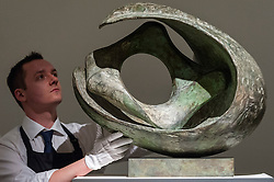 """© Licensed to London News Pictures. 18/11/2016. London, UK. A technician examines """"Curved Form With Inner Form (Anima)"""" by Dame Barbara Hepworth (est. GBP500-700k)"""", at the preview at Sotheby's of works on view at four upcoming November auctions featuring Modern & Post-War British Art, A Painter's Paradise (Julian Trevelyan & Mary Fedden at Durham Wharf), Scottish Art and Picasso Ceramics from the Lord & Lady Attenborough Private Collection. Photo credit : Stephen Chung/LNP"""