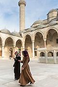 Muslim women in veil and modesty clothing in courtyard of Suleymaniye Mosque, Istanbul, Republic of Turkey