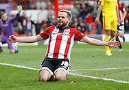 Brentford midfielder Alan Judge slides towards the fans to celebrate after his second goal of the game during the Sky Bet Championship match between Brentford and Rotherham United at Griffin Park, London, England on 17 October 2015. Photo by Andy Walter.