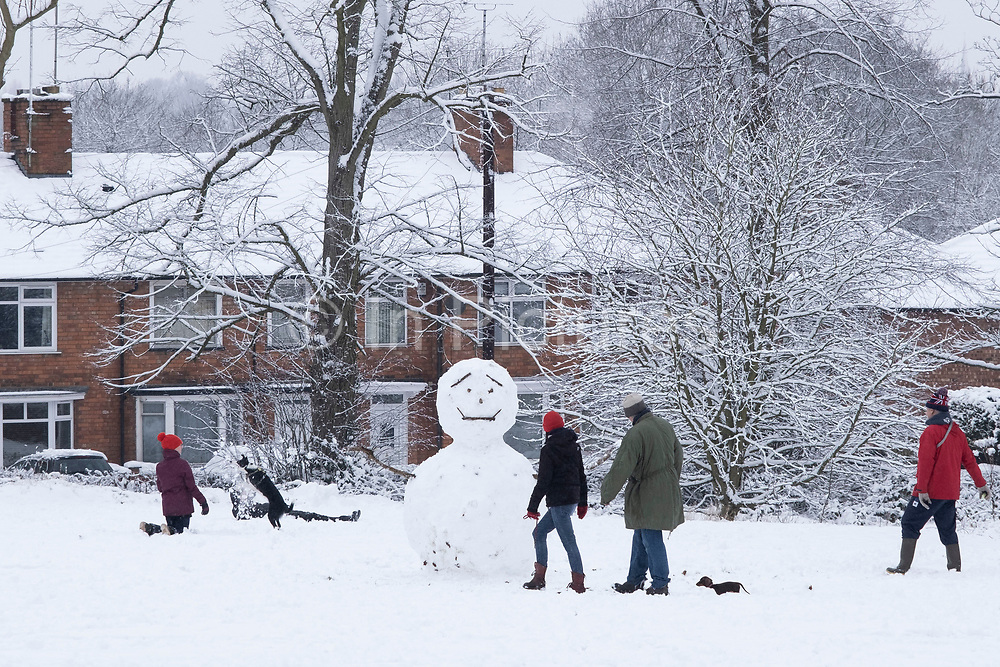 Local people enjoy playing and building a happy snow man in the snow in Highbury Park in Kings Heath on 24th January 2021 in Birmingham, United Kingdom. Deep snow arrived in the Midlands giving some light relief and fun during the current lockdown for people who simply enjoyed the weather.