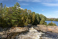 The rocky shoreline next to the Chute Aux Bleuets (Blueberry Falls) on the Rivière-Rouge (Red River) in the Village of Brébeuf, Québec, Canada.