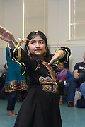 Dance student Preeti Tanwani, 8, demonstrates Nachale: The Bollywood Dance Workout, during the English Conversation Club: Dance and Dialogue event Saturday April 9, 2011 at the Iroquois Branch of the Louisville Free Public Library in Louisville, Ky. Henna and Bindi followed the Bollywood dance lesson, and then volunteers were paired with English language learners to work on conversation skills. (Photo by Brian Bohannon)