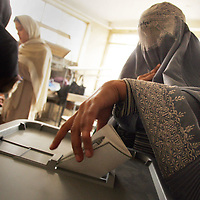 09 October 2004&#xD;&#xA;Kabul, Afghanistan.&#xD;&#xA;Presidential elections in Afghanistan.&#xD;&#xA;&#xD;&#xA;Afghanistans historic Presidential elections saw both men and women heading to the polling stations. Many of the women were wearing traditional burka's. They had to lift the veils in order to have their identity checked before proceeding with their vote. Both men and women had their thumbnails painted to avoid repetitious voting. Reports circulated that the ink had not proved to be indelible and that voters were simply rubbing it off.&#xD;&#xA;&#xD;&#xA;By mid afternoon 15 candidates had pulled out of the running amidst allegations of fraud.<br />