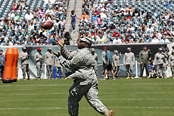 An Army serviceman catches a football on the field before the Philadelphia Eagles NFL football training camp practice in Philadelphia, Monday, August 5, 2013. (Photo by Brian Garfinkel)