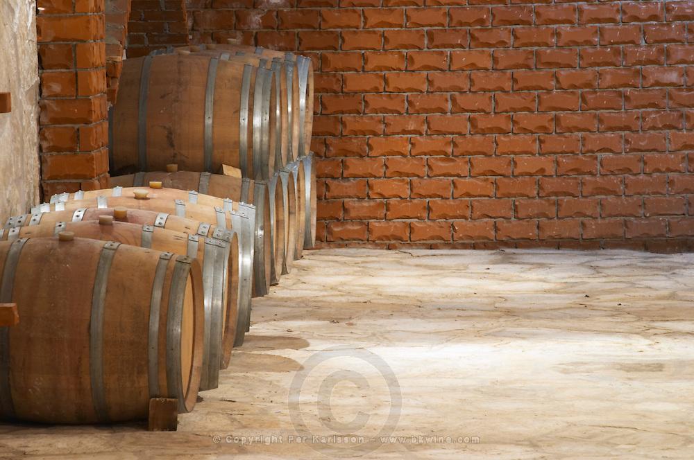 Wine cellar with oak barrels against red brick wall. Matusko Winery. Potmje village, Dingac wine region, Peljesac peninsula. Matusko Winery. Dingac village and region. Peljesac peninsula. Dalmatian Coast, Croatia, Europe.