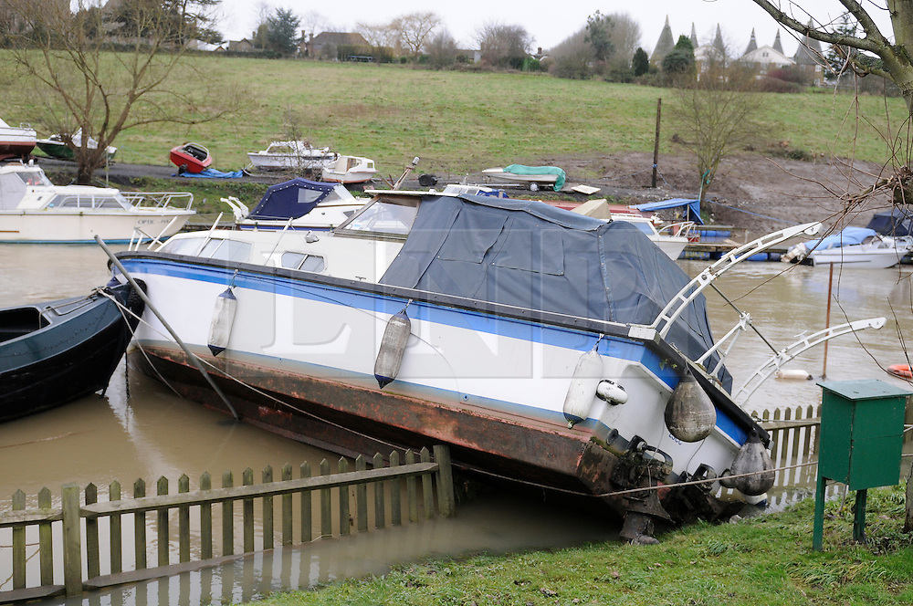 © Licensed to London News Pictures. 27/12/2013<br /> Damaged boat riverside at East Farleigh near Maidstone, Kent.<br /> East Farleigh flood water in Kent has receded leaving locals counting the cost of the damage.<br /> Flood water starts to recede over night across Kent.<br /> Photo credit :Grant Falvey/LNP