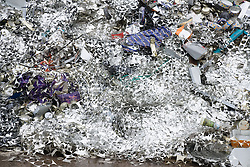 Pile of discarded residual tin sheets at a recycling centre,