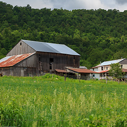 Bellville, PA, USA - May 23, 2013: An Amish farm with an unpainted barn near Belleville in Kishacoquillas Valley, Mifflin County, PA.