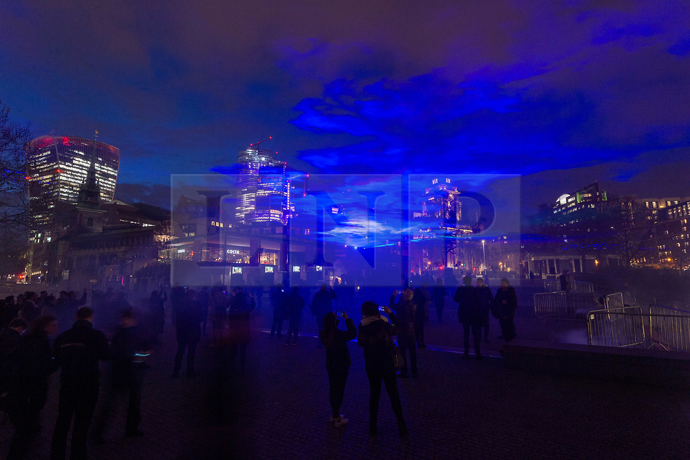 © Licensed to London News Pictures. 04/04/2019. London, UK. Artist Dan Acher recreates The Northern Lights over the Tower Hill area. The installation marked the launch of the new Huawei P30 series camera. London, UK. Photo credit: Ray Tang/LNP