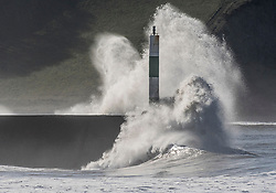 © Licensed to London News Pictures. 25/02/2019. Aberystwyth, UK. A big Atlantic swell, combined with the high tide, bring huge waves rolling in to the harbour lighthouse  in Aberystwyth on a sunny and warm February morning.. Photo credit: Keith Morris/LNP