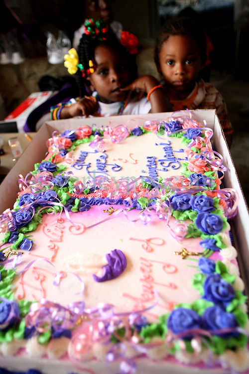 29 August 2007. Lower 9th Ward, New Orleans, Louisiana. <br /> Second anniversary of Hurricane Katrina. Grand children Chyana Hurst (4 yrs (l)) and Tyriq Burton (3 yrs) await cutting of a memorial cake inside Robert Lynn Green Sr's FEMA trailer  at 1826 Tennessee Street in the Lower 9th Ward. His house was destroyed by the deluge when the levee breached just blocks from the steps. Robert lost his mother and another grand daughter at the house when they perished in the terrible flooding. He lost hold of his grand daughter in the swirling floods. She was drowned. His mother was not found for 4 months when her skeleton was discovered in what remained of his washed away house. Jason hopes to rebuild. Many residents are struggling to return to the still derelict and decimated Lower 9th Ward.<br /> Photo credit; Charlie Varley.