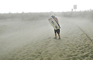 A boy shields himself from flying sand with a boogie board in Ocean City during fast moving thunder storm early Thursday evening.