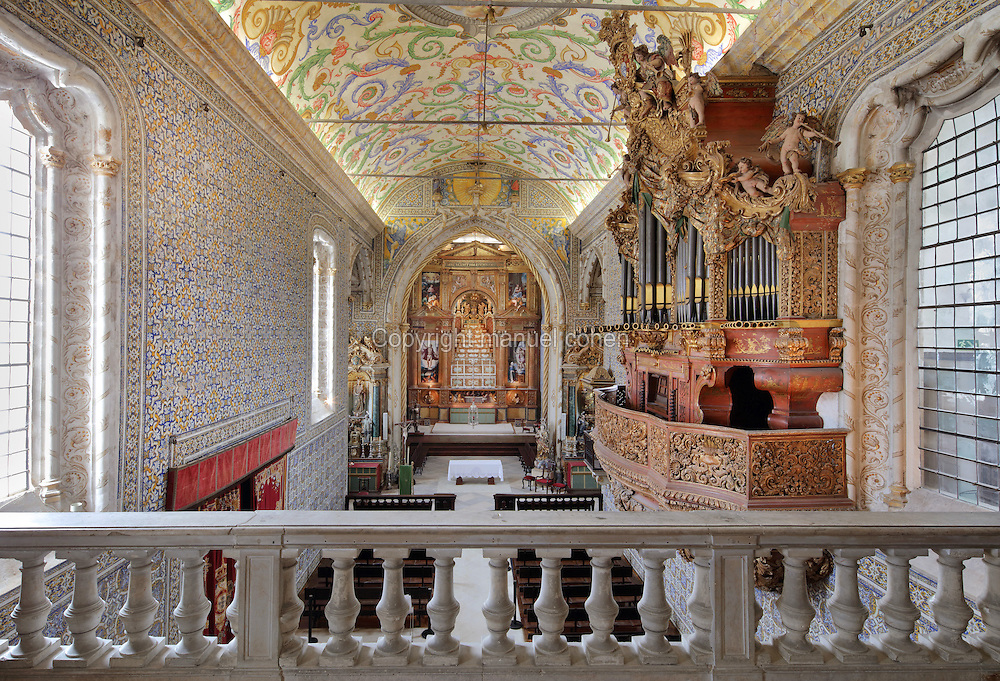 Sao Miguel Chapel, or St Michael's Chapel, seen from the balcony, designed in Manueline style 1517-22 by Marco Pires and completed by Diogo de Castilho, on the site of a 12th century chapel in the University of Coimbra, Coimbra, Portugal. In the chancel is the Mannerist altarpiece, designed by Bernardo Coelho in 1605 and made by sculptor Simon Mota, with paintings by Simon Rodrigues and Domingos Vieira Serrao. The chapel was renovated in the 17th and 18th centuries, with Manuel Ramos making the pulpit in 1684, ceiling painted by Francisco F de Araujo, tiled floor added 1613, Baroque organ with 2,000 pipes built 1733 by Fray Manuel de Sao Bento (right), and Gabriel Ferreira da Cunha painting chinoiserie elements in 1737. The University of Coimbra was first founded in 1290 and moved to Coimbra in 1308 and to the royal palace in 1537. The building is listed as a historic monument and a UNESCO World Heritage Site. Picture by Manuel Cohen