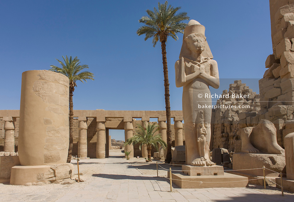 A landscape void of tourists of the giant colossus of Pharaoh Ramesses ll and Bintanat at the ancient Egyptian Temple of Karnak, Luxor, Nile Valley, Egypt. According to the country's Ministery of Tourism, European visitors to Egypt  is down by up to 80% in 2016 after the suspension of flights after the downing of the Russian airliner in Oct 2015. Euro-tourism accounts for 27% of the total flow and in total, tourism accounts for 11.3% of Egypt's GDP.
