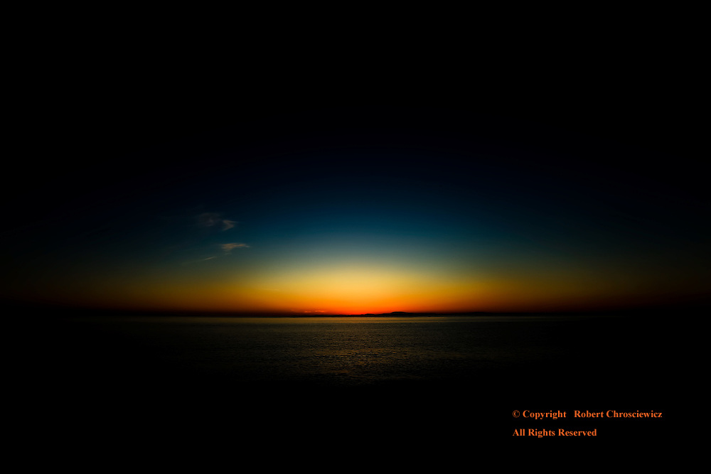 Sunset Eye: Sunset over the Pacific Ocean dramatically merges with the night, Whitby Island Washington, United States of America.