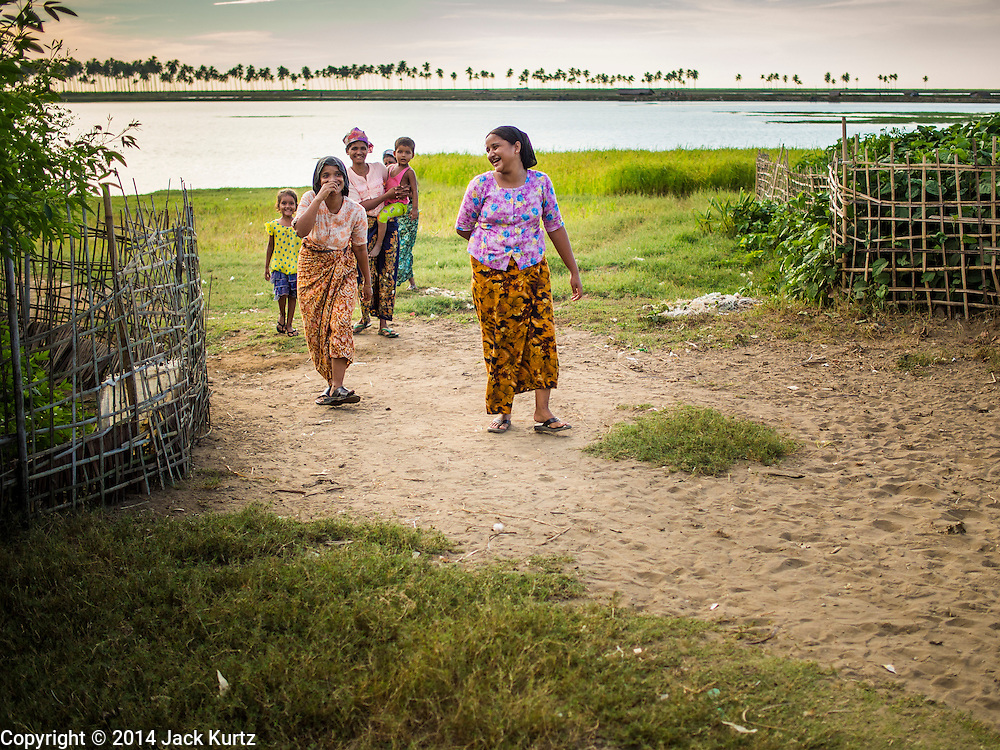 05 NOVEMBER 2014 - SITTWE, RAKHINE, MYANMAR: Rohingya Muslim women walk back to the Rohingya Muslim IDP camp they live in near Sittwe. After sectarian violence devastated Rohingya communities and left hundreds of Rohingya dead in 2012, the government of Myanmar forced more than 140,000 Rohingya Muslims who used to live in and around Sittwe, Myanmar, into squalid Internal Displaced Persons camps. The government says the Rohingya are not Burmese citizens, that they are illegal immigrants from Bangladesh. The Bangladesh government says the Rohingya are Burmese and the Rohingya insist that they have lived in Burma for generations. The camps are about 20 minutes from Sittwe but the Rohingya who live in the camps are not allowed to leave without government permission. They are not allowed to work outside the camps, they are not allowed to go to Sittwe to use the hospital, go to school or do business. The camps have no electricity. Water is delivered through community wells. There are small schools funded by NOGs in the camps and a few private clinics but medical care is costly and not reliable.   PHOTO BY JACK KURTZ