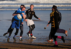 © Licensed to London News Pictures. <br /> 28/12/2014. <br /> <br /> Saltburn, United Kingdom.<br /> <br /> A group of friends enjoy a game of touch rugby at Saltburn beach on a freezing cold morning on Teesside.<br /> <br /> Photo credit : Ian Forsyth/LNP