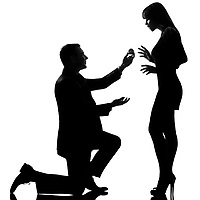 one caucasian couple man kneeling offering engagement ring and woman surprised in studio silhouette isolated on white background