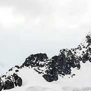 A rugged rocky mountain range at Paradise Harbor in Antarctica, with steep rocky cliffs rising out of the ice and snow.