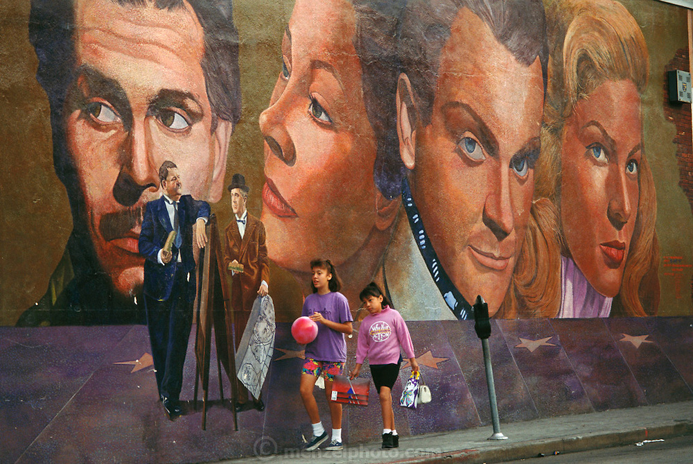 Two girls walk past a mural on Hollywood Boulevard. Shot for the book project: A Day in a Life of Hollywood. Hollywood, California. USA.
