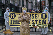 """March 17, 2020, London, England, United Kingdom: Activists of """"Pause the System"""" group holding placards during a symbolic protest in front of number ten Downing Street in London on Tuesday, Mar 17, 2020. The group is demanding the government to follow the World Health organisation's rules and get involved with enforcing isolation to prevent the spread of coronavirus across the country. (Credit Image: © Vedat Xhymshiti/ZUMA Wire)"""