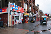 Man taking a cogarette break outside shops near the underpas at Holloway Circus in Birmingham city centre, which is virtually deserted under Coronavirus lockdown on a wet rainy afternoon on 28th April 2020 in Birmingham, England, United Kingdom. Britains second city has been in a state of redevelopment for some years now, but with many outdated architectural remnants still remaining, on a grey day, the urban landscape appears as if frozen in time. Coronavirus or Covid-19 is a new respiratory illness that has not previously been seen in humans. While much or Europe has been placed into lockdown, the UK government has put in place more stringent rules as part of their long term strategy, and in particular social distancing.