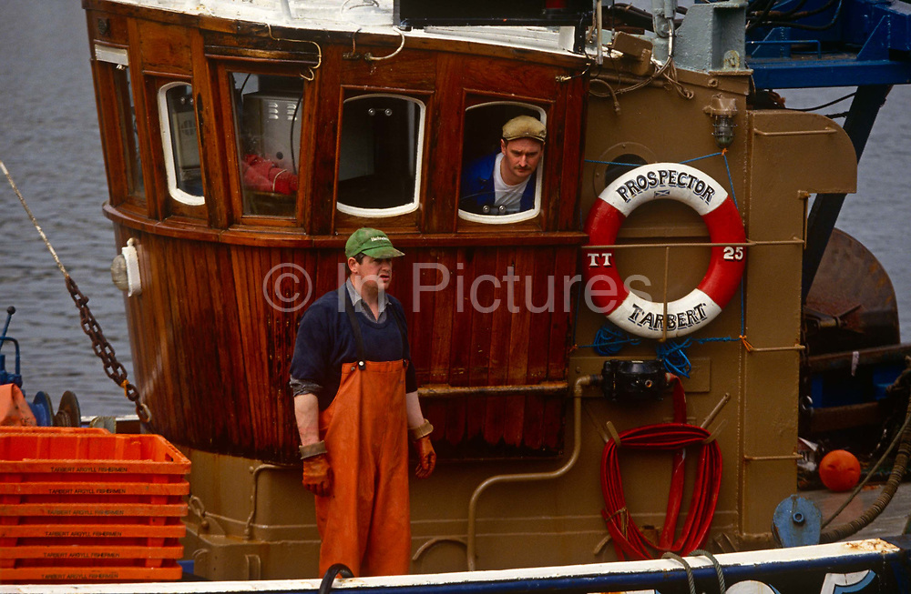 Two fishermen return to their home port of Tarbert on the western Scottish Mull of Kintyre. Looking towards the quay that will receive their boat called Prospector and where they are to unload their catch of shrimp, one man is the skipper and he steers the vessel from the wheelhouse while his partner at sea, wears chest-high waders and matching rubber gloves that can handle fish and sea creatures they drag up from the Atlantic waters. The boat has its identifying letters and number on its hull TT25 as well as on the life-ring it carries by law. The men probably support their families and so are the breadwinners - their livelihoods dependent of fisheries policy and EU quotas that dictate how much they're allowed to catch per day/per week. But they are safe after a period at sea and appear happy to have returned with a catch to sell.