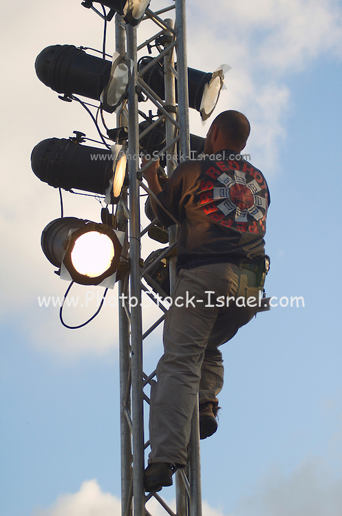an electrician fixing the outdoor stage lighting