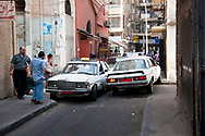 Tripoli, Lebanon - September 7, 2010: Taxis on a narrow city street use the sidewalk to squeeze past each other. Tripoli is the largest city in northern Lebanon, and the second largest city in the country after Beirut.