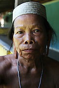 August 2012: Kenyah native woman, Gin whom I photographed in 1991 in Long Geng, now living in Long Lewan over two decades later. Long Lewan is above the waterline, whilst Long Geng is below, and was flooded by the Bakun Dam. Long Lewan, Belaga district, Sarawak, Borneo<br /> <br /> Their community is now dispersed between Sungai Asap, Long Lewan and floating longhouses on the Bakun reservoir. The Bakun hydro-electric dam, which covers 700km². Construction of the dam required the relocation of more than 9,000 native residents, mainly Kayan and Kenyah indigenous peoples who lived in the flooded area. Many Sarawak natives have been relocated to a longhouse settlement named Sungai Asap in Bakun. Most of them were subsistence farmers. Each family were promised only 3 acres of land, insufficient to survive, and many families still have not been compensated for the loss of their longhouses..Sarawak's primary rainforests have been systematically logged over decades, threatening the sustainable lifestyle of its indigenous peoples who relied on nomadic hunter-gathering and rotational slash & burn cultivation of small areas of forest to survive. Now only a few areas of pristine rainforest remain; for the Dayaks and Penan this spells disaster, a rapidly disappearing way of life, forced re-settlement, many becoming wage-slaves. Large and medium size tree trunks have been sawn down and dragged out by bulldozers, leaving destruction in their midst, and for the most part a primary rainforest ecosystem beyond repair. Nowadays palm oil plantations and hydro-electric dam projects cover hundreds of thousands of hectares of what was the world's oldest rainforest ecosystem which had some of the highest rates of flora and fauna endemism, species found there and nowhere else on Earth, and this deforestation has done irreparable ecological damage to that region.