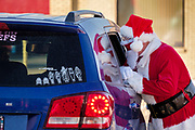 "05 DECEMBER 2020 - INDIANOLA, IOWA: STAN THOMPSON, dressed as Santa Claus, talks to children in their car during a drive through visit with Santa Claus. This is the seventh year the Thompsons have dressed as the Clauses to entertain the children of Indianola. About 500 children visited Santa Claus and Mrs. Claus in Indianola Saturday. The town has hosted Santa on the town square for the last seven years but the COVID-19 (SARS-Cov-2) pandemic forced organizers to move the event to the parking lot of a local hardware store and do it ""drive through"" style. Iowa has one of the highest Coronavirus test rates in the United States.        PHOTO BY JACK KURTZ"