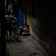 Children study  by the precious streaks of daylight in the alleyways of Dharavi.