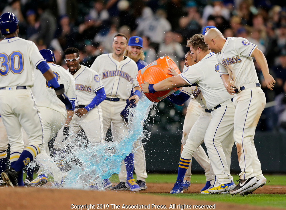 Seattle Mariners' Daniel Vogelbach attempts to dump ice on Tom Murphy (2), left, after Murphy drew a bases loaded walk to win 11-10 over the Chicago White Sox in a baseball game, Sunday, Sept. 15, 2019, in Seattle. (AP Photo/John Froschauer)